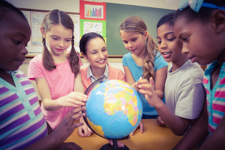 world of work: Teacher and pupils looking at globe at the elementary school