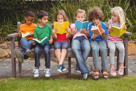 niños sentados: Niños que leen en los libros juntos mientras se está sentado