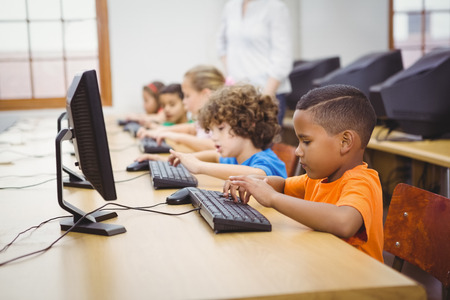 computer monitor: Students using computers in the classroom at the elementary school Stock Photo