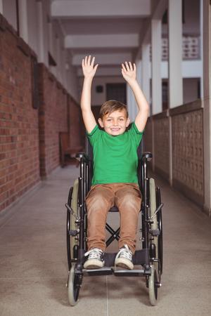 paraplegico: Estudiante sonriente en una silla de ruedas con los brazos levantados en los terrenos de la escuela primaria