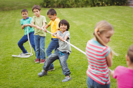 sexes: Cute pupils playing tug of war on the grass outside on elementary school campus