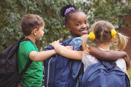 nene y nena: Estudiantes sonrientes mirando a la cámara en los terrenos de la escuela primaria Foto de archivo