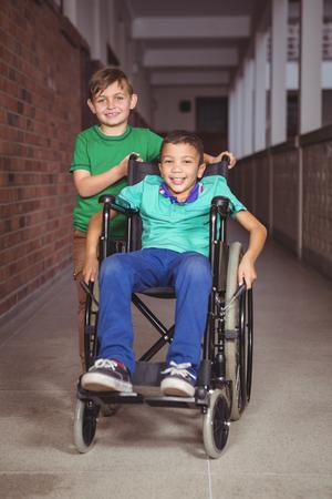 paraplegic: Estudiante sonriente en silla de ruedas y amigo a su lado en los terrenos de la escuela primaria Foto de archivo