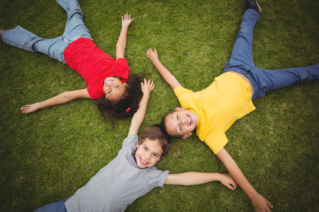 schoolmate: Cute pupils lying on grass smiling on elementary school campus