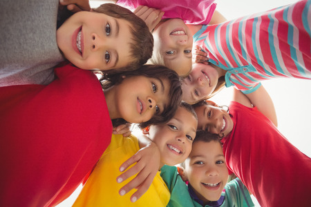 recess: Cute pupils in a huddle on elementary school campus Stock Photo