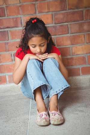 solitariness: Upset lonely girl sitting by herself on the elementary school grounds Stock Photo