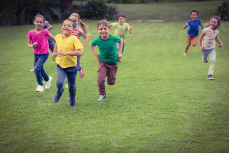 school campus: Cute pupils running towards camera on elementary school campus Stock Photo