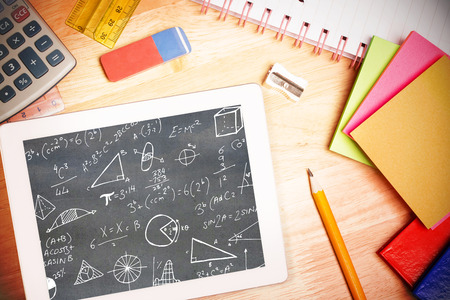 with difficulty: Math equations against students desk with tablet pc