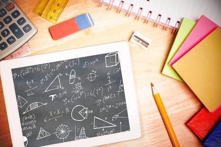 Wiskundige vergelijkingen tegen studenten Bureau met tablet pc Stockfoto