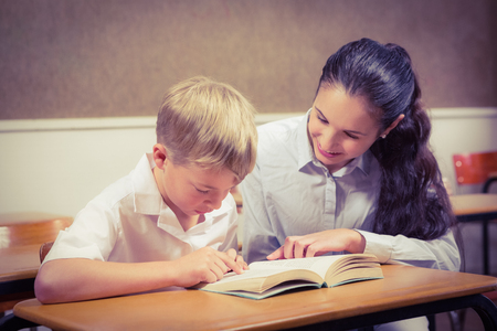 child reading book: Teacher helping a student in class at the elementary school Stock Photo