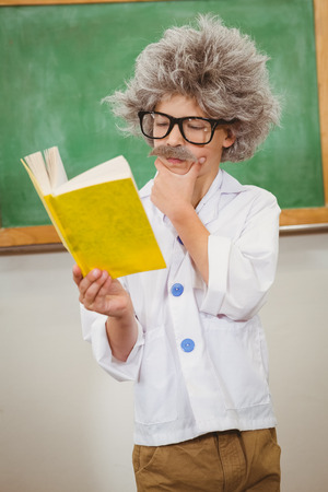 make believe: Student dressed up as einstein reading a book at the elementary school Stock Photo
