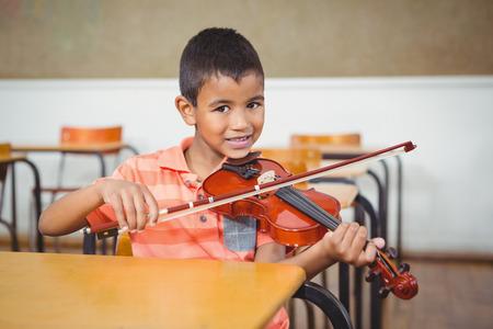 ni�os jugando: Estudiante que usa un viol�n en la clase en la escuela primaria