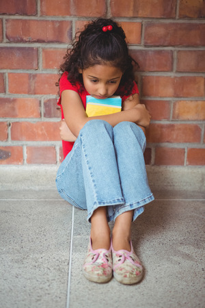 lonesomeness: Upset lonely girl sitting by herself on the elementary school grounds Stock Photo