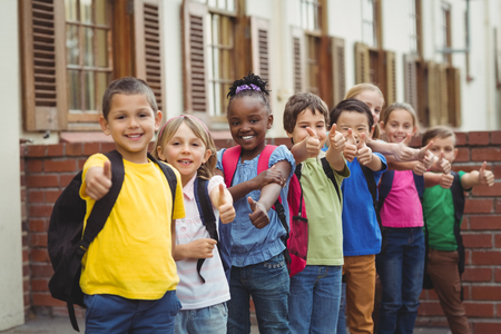 pupils: Cute pupils with schoolbags outside on elementary school campus