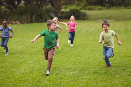 niño corriendo: Alumnos lindas corriendo hacia la cámara en el campus de la escuela primaria Foto de archivo