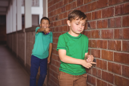 bullying: Student being bullied by a fellow student on the elementary school grounds Stock Photo
