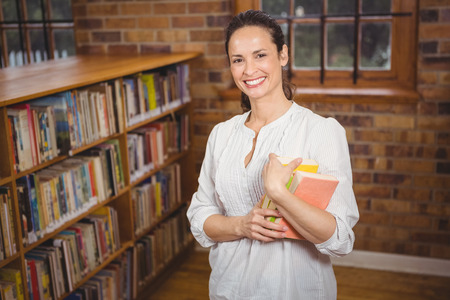 teaching adult: Smiling teacher holding books in her hands at the elementary school