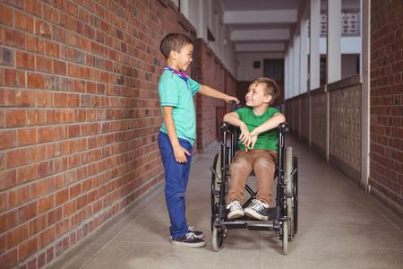 paraplegico: Estudiante sonriente en silla de ruedas y amigo a su lado en los terrenos de la escuela primaria Foto de archivo