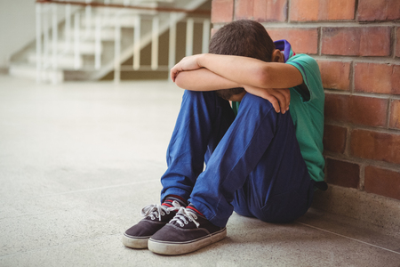 Upset lonely child sitting by himself on the elementary school grounds