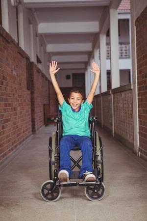 paraplegic: Estudiante sonriente en una silla de ruedas con los brazos levantados en los terrenos de la escuela primaria