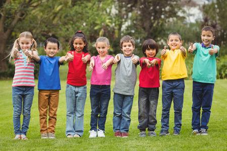 Милые ученики, указывая на камеру на начальной кампусе школы Фото со стока