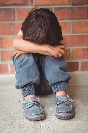 desolaci�n: Malestar ni�o solitario sentado solo en los terrenos de la escuela primaria