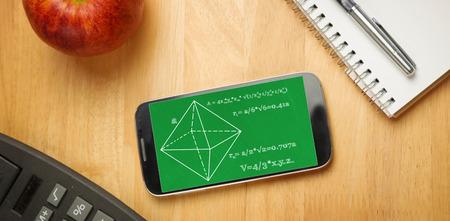 matematicas: Los problemas de matem�ticas en contra de tel�fono inteligente en el escritorio Foto de archivo