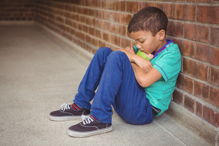 solitariness: Upset lonely child sitting by himself on the elementary school grounds