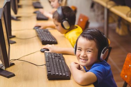 escuela primaria: Alumnos lindos en la clase de computaci�n en la escuela primaria