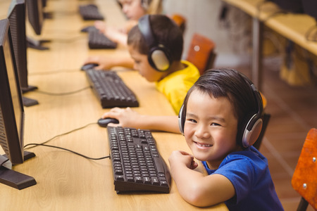 girls back to back: Cute pupils in computer class at the elementary school