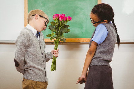make believe: Student giving flowers to another student at the elementary school