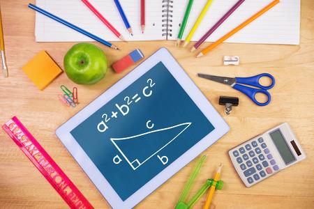 matemáticas: Trigonometría contra la mesa de los estudiantes con útiles escolares