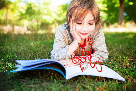 jumble: letter and number jumble against cute little boy reading in park Stock Photo