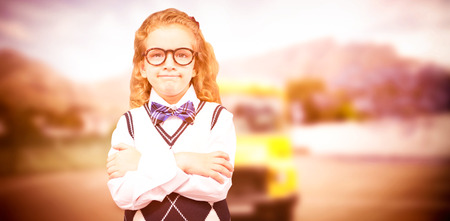 autobus escolar: Cute pupil with arms crossed against yellow school bus waiting for pupils