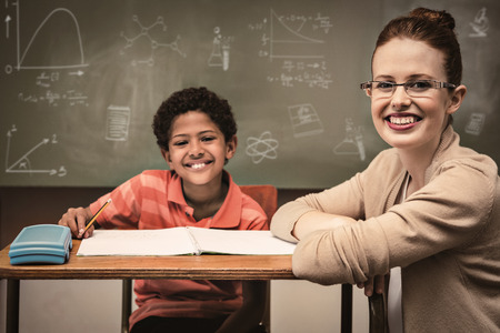 Math and science doodles against teacher assisting little boy with homework in classroom Stock Photo