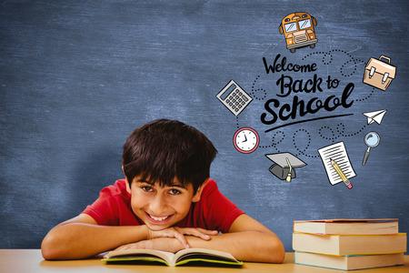 higher intelligence: Portrait of boy reading book in library against blue chalkboard