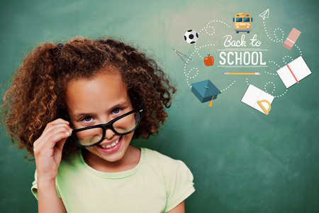 Cute pupil tilting glasses against back to school Stock Photo