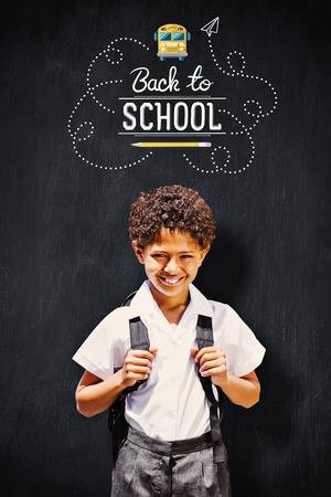 first day of school: Cute pupil smiling at camera by the school bus against blackboard Stock Photo