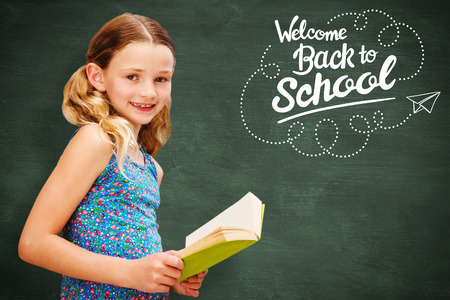 higher intelligence: Girl reading book in library against green chalkboard Stock Photo