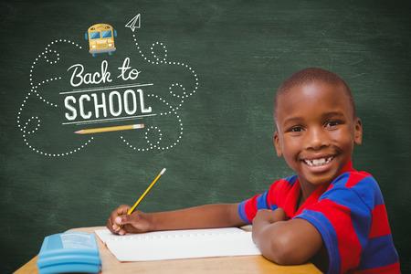 niños negros: pupila feliz en el escritorio frente a la pizarra verde
