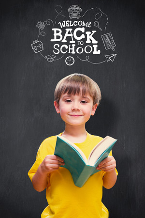 kid book: happy pupil with book against blackboard Stock Photo