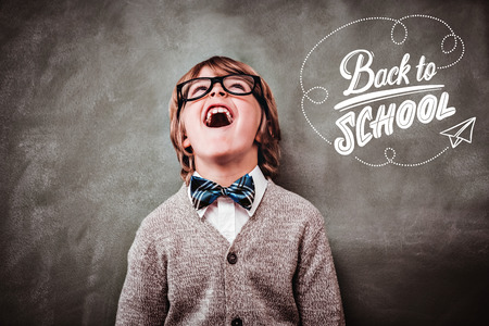 back to school against boy laughing in front of blackboard
