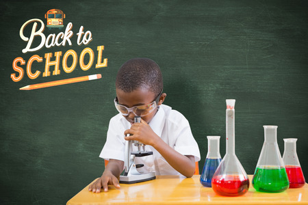 make believe: Cute pupil playing scientist against green chalkboard
