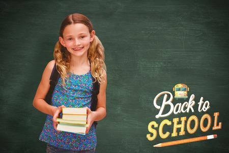 higher intelligence: Cute little girl holding books in library against green chalkboard Stock Photo