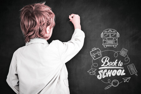 Cute pupil writing on board against back to school