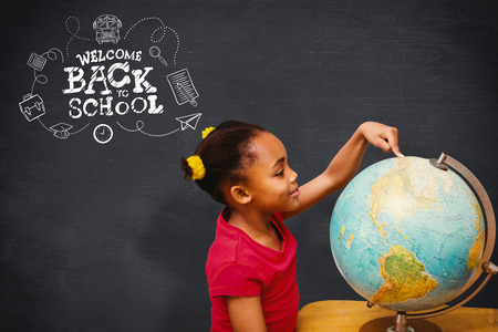 pupil: Happy pupil with globe against blackboard