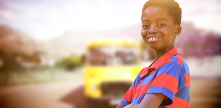 coach bus: Cute little boy smiling at camera against yellow school bus waiting for pupils Stock Photo
