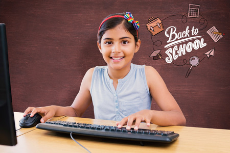 school child: School kid on computer against desk Stock Photo