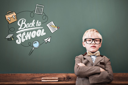 make believe: back to school against cute pupil dressed up as teacher in classroom Stock Photo