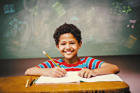 reading and writing: School subjects doodles against little boy writing book in classroom Stock Photo